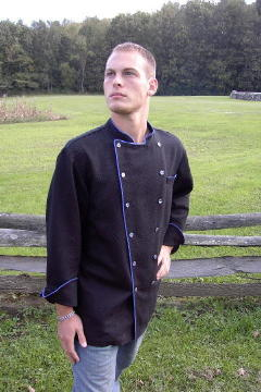 Chef Coat Style BSM100: Shown in Black 100% cotton petti point pique, left chest tailored welt pocket, blue suede piping (collar, front, cuffs, & pocket) & blue mussel buttons.