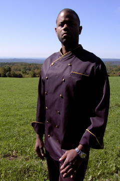 Chef Coat Style CBM101: Shown in Black, 100% cotton Supima® gabardine, left chest tailored welt pocket, cheviot gold piping (collar, cuffs & pocket) & brass buttons.