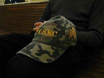 "Yupoong Flexfit® Camouflage Cap with USMC in ""stencil"" font, Fleur de lis and Sergeant Chevrons with ""puff"" embroidery in Ginger thread color."