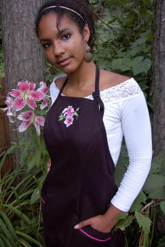 Women's Bib apron style W740; Shown in black, 100% cotton gabardine with two side hip tailored welt pockets, Ruby Glint piping on pocket welts, & embroidered stargazer lilies on center chest.