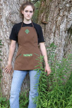 Women's Bib apron style W740 shortened 5 inches; Shown in Nutmeg, 100% cotton denim with two side hip tailored welt pockets, kelly piping on pocket welts, embroidered Celtic Knot on center chest & embroidered vine design on center stomach.