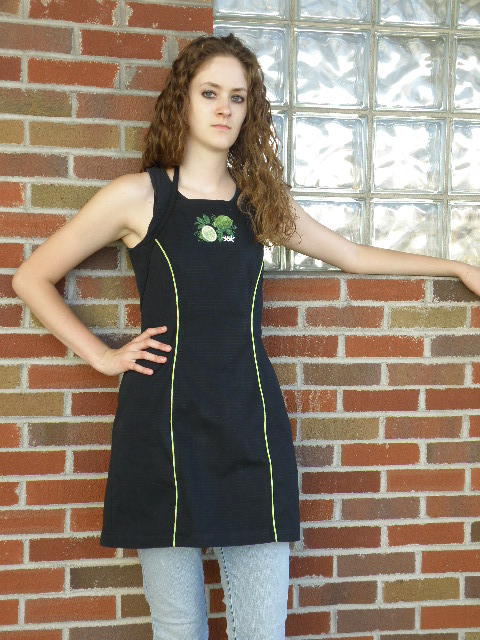 Women's Bib apron style W740; Shown in black, 100% cotton Ripstop with Lime piping along princess seams, & embroidered Lime Botanical on center chest.