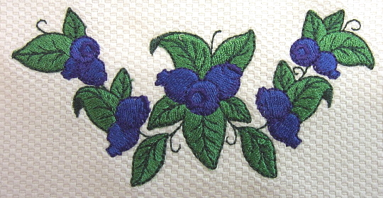 Close up image of embroidered blueberry wreath. Shown on 100% cotton petti point pique.