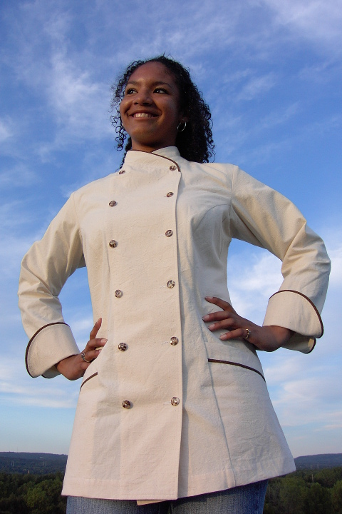 Women's Chef Coat Style BSW101: Shown in Natural, 100% Combed Cotton Ripstop, date piping (collar, pockets & cuffs), two front hip tailored welt pockets & tiger shell buttons.
