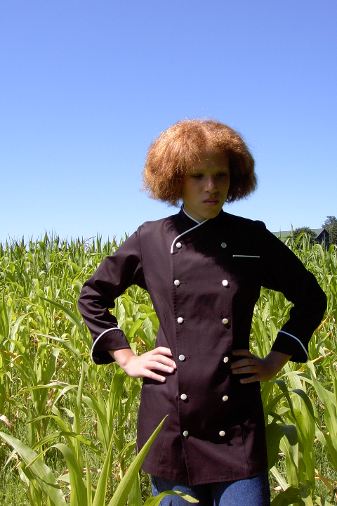 Women's Chef Coat Style CBW101: Shown in Black, 100% Cotton Supima® gabardine, natural white piping (collar, pocket & cuffs), left chest tailored welt pocket & faux mother-of-pearl buttons.