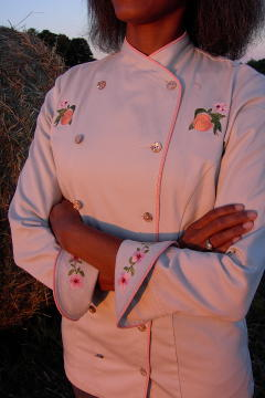 Women's Chef Coat Style BSW101: Shown in Ivory, 100% cotton Denim, bisque piping (collar, front & cuffs), Peach botanicals (one embroidered on each chest), peach blossom chains (one embroidered on each cuff) & awabi buttons.