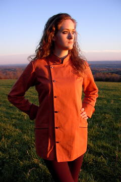 Women's Chef Coat Style BSW102: Shown in Terra Cotta, 100% cotton denim, black piping (collar, front, cuffs & pockets), two front hip tailored welt pockets, kissing collar & pin shank buttons.