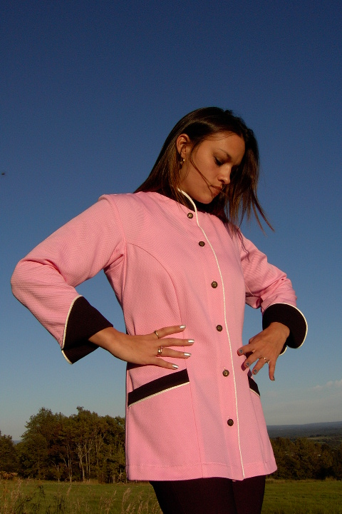 Women's Chef Coat Style BSW103: Shown in pink & black, 100% cotton petti point pique, ivory piping (collar, front, cuffs & pockets) two front hip tailored welt pockets, & metal on black horn horse head buttons.