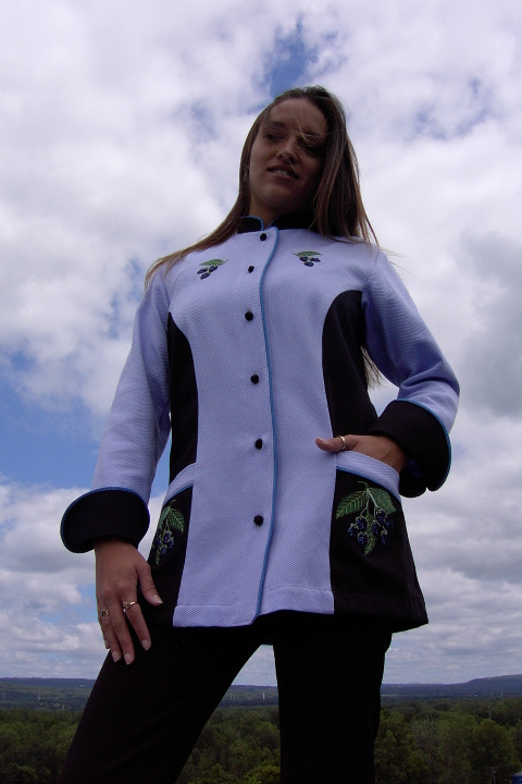 Women's Chef Coat style BSW104; Shown in Lavender & black, 100% cotton petti point pique & 100% cotton Gabardine, two front hip tailored welt pockets, Copen piping (collar, front, cuffs & pockets), Black Gabardine, hand tied knot buttons & blackberry embroideries on the chests, pockets, & back of collar.