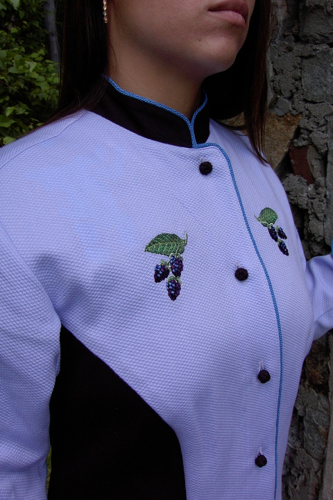 Close up image of small blackberry embroidery on the chest of Women's Chef Coat style BSW104; Shown in Lavender & black, 100% cotton petti point pique & 100% cotton Gabardine, two front hip tailored welt pockets, Copen piping (collar, front, cuffs & pockets), Black Gabardine, hand tied knot buttons & blackberry embroideries on the chests, pockets, & back of collar.