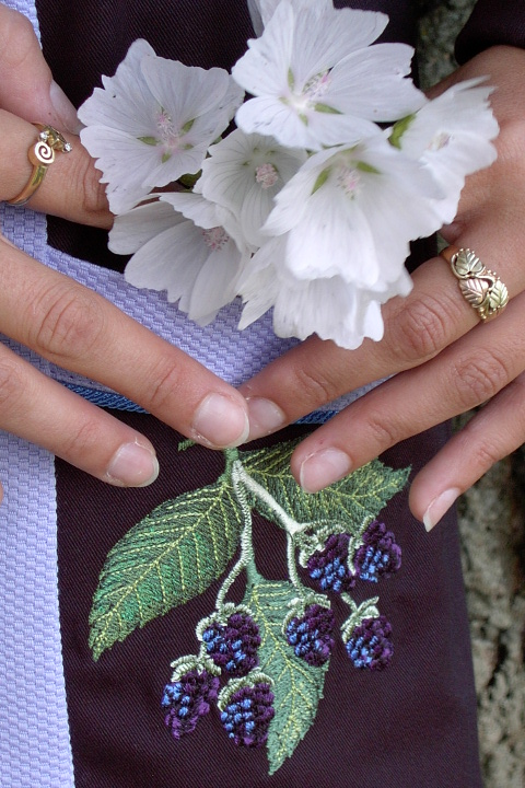 Close up image of blackberry embroidery on the pocket of Women's Chef Coat style BSW104; Shown in Lavender & black, 100% cotton petti point pique & 100% cotton Gabardine, two front hip tailored welt pockets, Copen piping (collar, front, cuffs & pockets), Black Gabardine, hand tied knot buttons & blackberry embroideries on the chests, pockets, & back of collar.