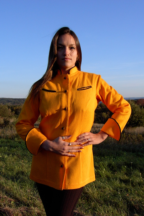 Women's Chef Coat Style BSW104: Shown in orange, 100% cotton honeycomb pique, left & right chest curved double welt pockets, black piping (collar, cuffs & pockets) & hand tied knot buttons.