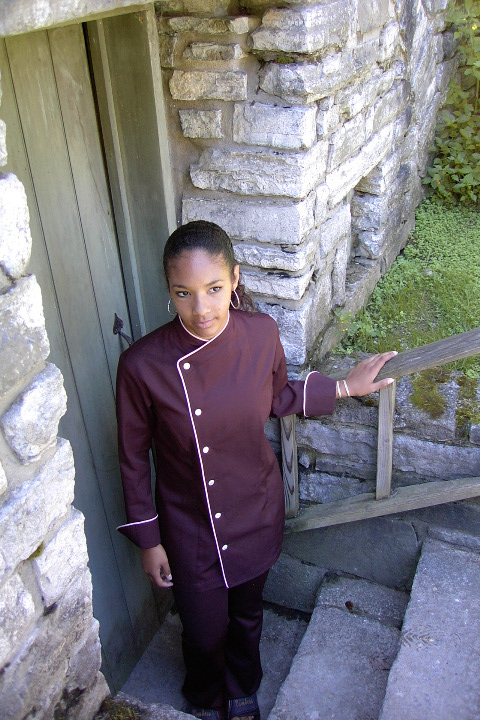 Women's Chef Coat Style CBW105: Shown in Black, 100% cotton gabardine, with a left sleeve tailored welt pocket, Pink Sham piping (cuffs, collar & front) & faux Mother-of-Pearl buttons.