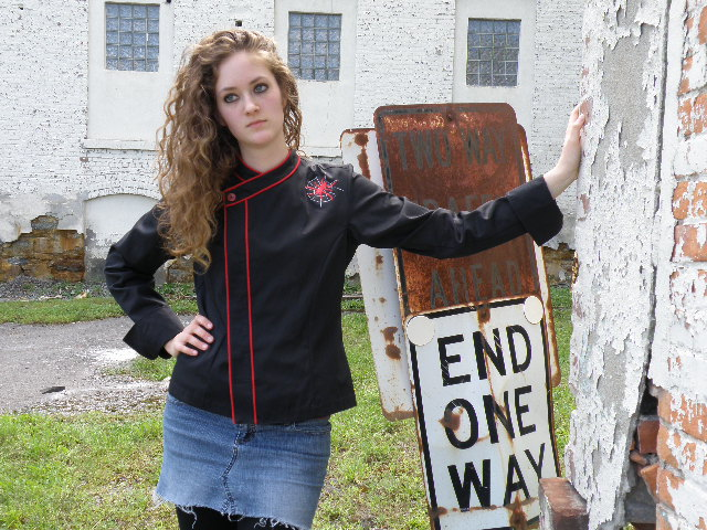 Cropped Women's Jacket Style CBW105H; Shown in black 100% cotton Supima® Gabardine with two rows of Foxy Red piping along the collar and placket, one red tagua nut top button, spider embroidery on left front shoulder and square cuffs.