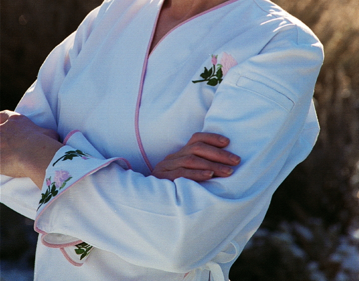 Close-up image of rose embroidery on cuffs, and left chest, of Women's Chef Coat Style BSW106: Shown in White, 100% cotton gabardine, Pink Sham piping (cuffs, collar & front), left sleeve tailored welt pocket & Rose embroidery (3 on each cuff & one on the left chest).