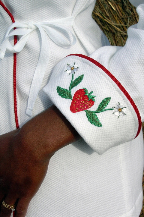 Women's Chef Coat Style BSW106: Shown in White, 100% cotton petti point pique, red berry piping (cuffs, collar & front), & strawberries & flowers embroidery (one on each cuff).Women's Chef Coat Style BSW106: Shown in White, 100% cotton petit point pique, red berry piping (cuffs, collar & front), & strawberries & flowers embroidery (one on each cuff).